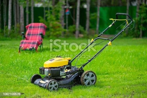 istock Mower standing on green grass on yard. 1062100576