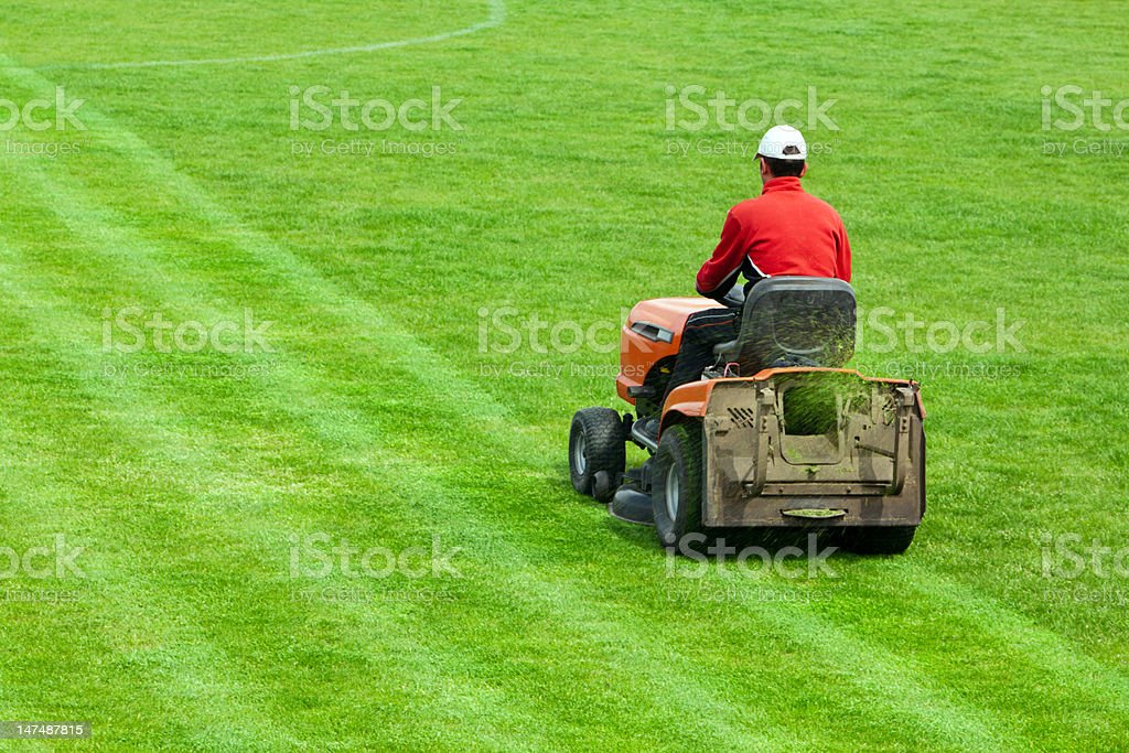 Mowing grass in stadium stock photo