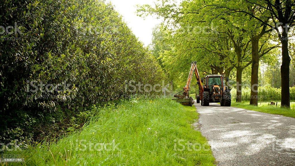 mowing grass shoulder with tractor mower stock photo