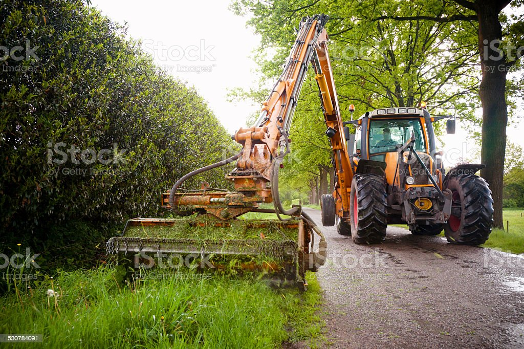mowing grass verge  with tractor mower stock photo