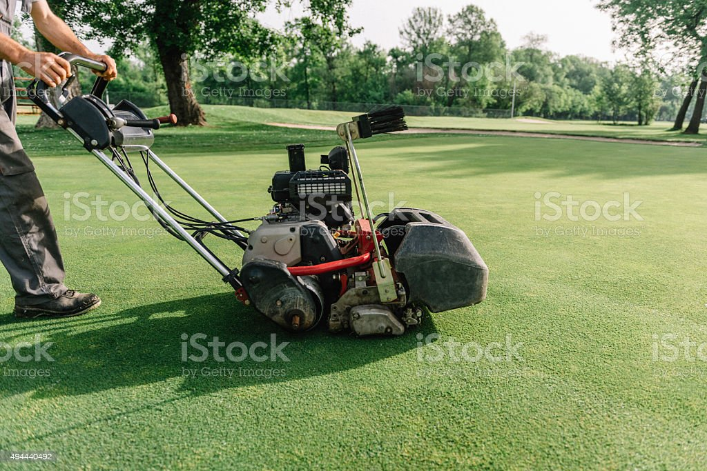 Mowing greens at the golf course stock photo
