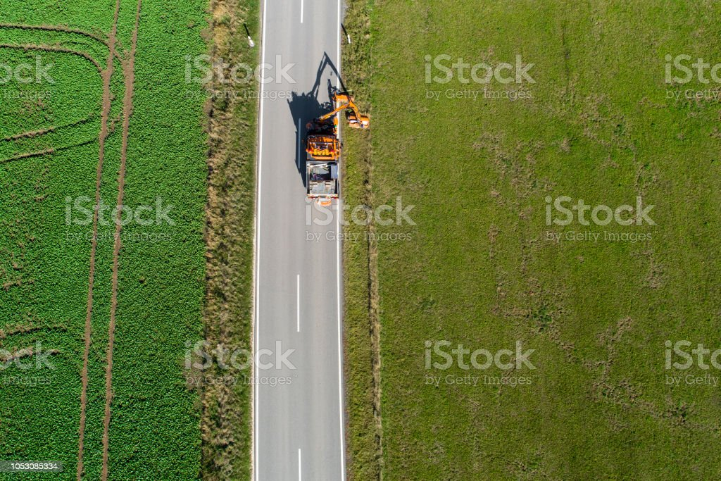 Mowing operations on a country road - aerial view