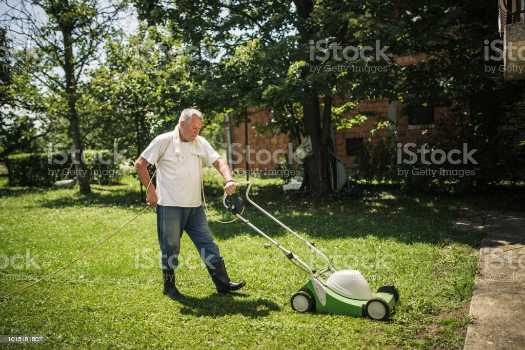 One senior man, mowing the lawn with lawnmower in his back yard.