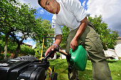 Focus on lawn mower. Young man mowing the lawn a sunny day in Sweden. Garden with flowers in background.