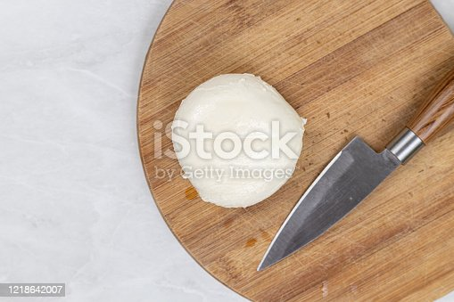 Mozarella cheese on the cutting wooden board with knife.