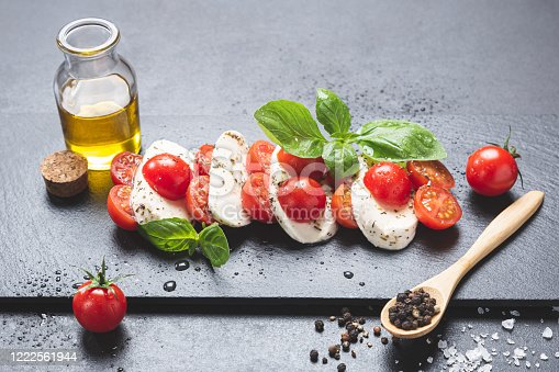 Mozzareela, tomato and basil, on blackboard on black background,  with extra virgin olive oil, salt and pepper.  Mediterranean diet  and healthy food concept