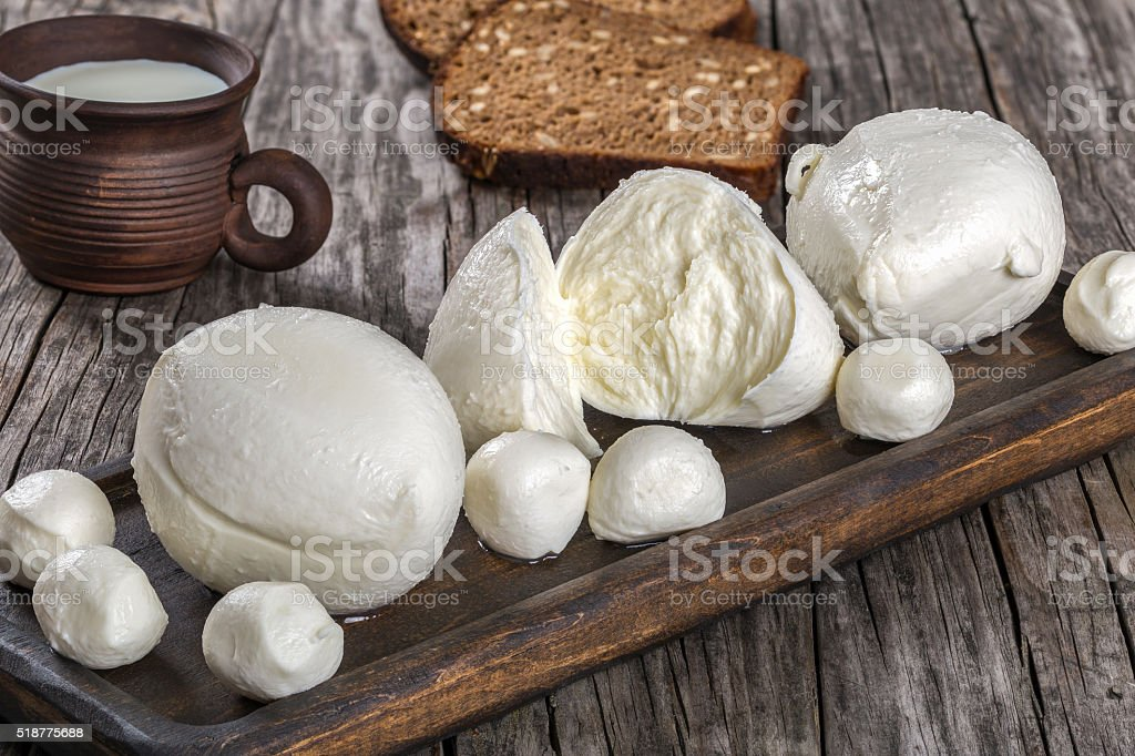 mozzarella balls and clay cup with milk stock photo