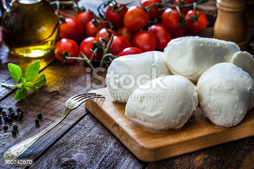 Mozzarella cheese on a cutting board shot on rustic wooden table. On the table all around the board are ingredients for preparing Caprese salad like tomatoes, olive oil, basil, pepper and salt. Low key DSRL studio photo taken with Canon EOS 5D Mk II and Canon EF 100mm f/2.8L Macro IS USM
