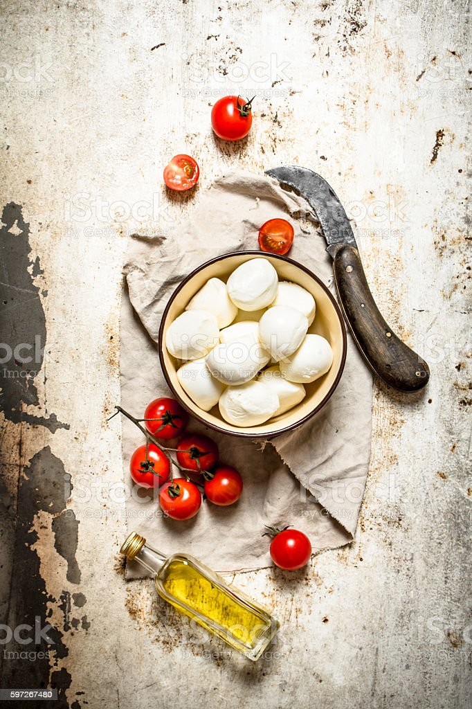 Mozzarella cheese, tomatoes, olive oil and an old knife. royalty-free stock photo
