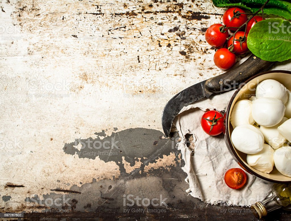 Mozzarella cheese, tomatoes, olive oil and an old knife. Lizenzfreies stock-foto