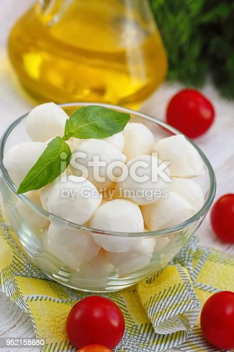 Small mozzarella balls, cherry tomatoes and fresh greens - ingredients for caprese salad