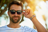 Portrait of a handsome young man wearing sunglasses on a summer's day outdoors