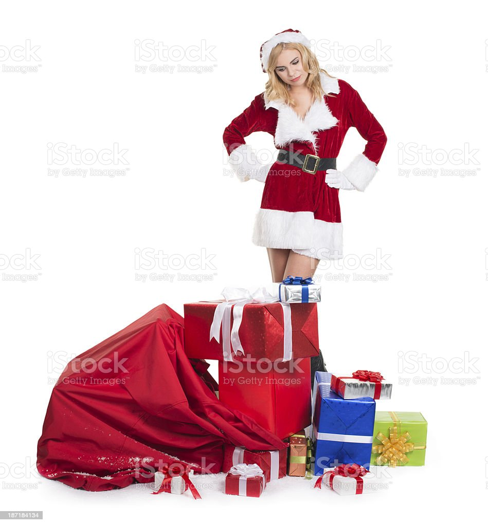 Mrs. Claus is looking at bag full of gifts. stock photo