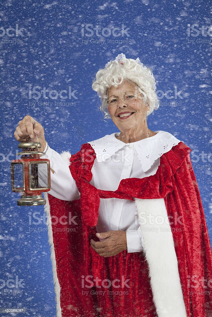 Mrs Clause standing in the snow holding a lantern stock photo