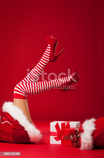 istock Mrs santa claus legs in striped stockings with christmas gifts 186348266