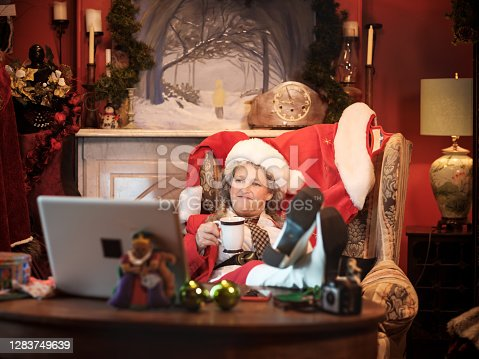 Mrs.Clause using a computer in Santa's study to do a Christmas video conference. She  holding a mug with hot beverage.