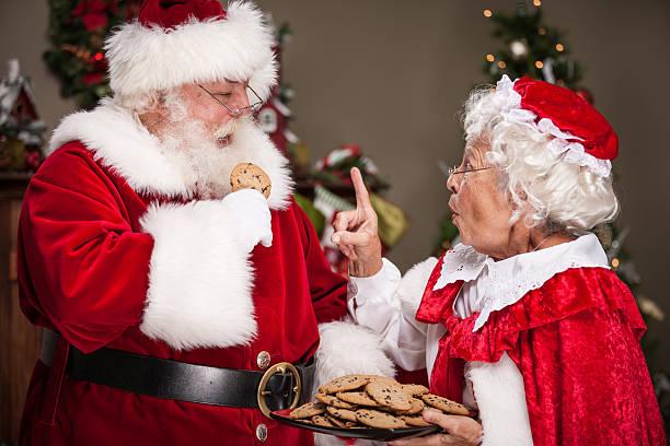 Frau Weihnachtsmann Scolds Santa Claus zum Essen zu viele Cookies – Foto