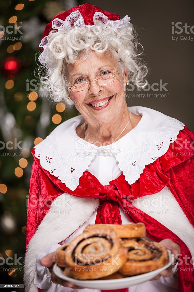 Ms. Claus With Plate of Cinnamon Rolls stock photo