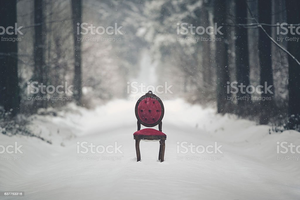 msystic scene with red chair in a winter forest stock photo