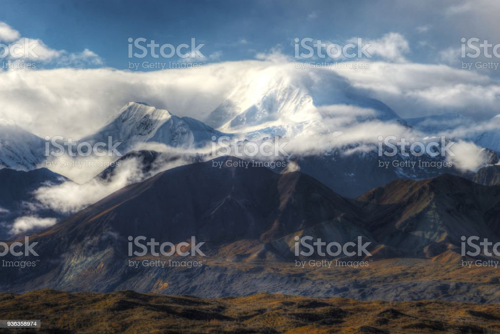 Mt. Deanli shows his head above the clouds and fog. stock photo