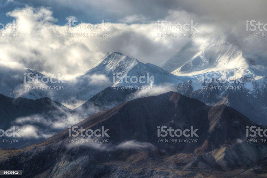 Mt. Denali Mountain shines beneath fog and snow. stock photo