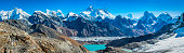 Panoramic view from the Renjo La over Gokyo Lake and Sherpa village to the Everest range high in the Sagarmatha National Park of the Nepalese Himalayas, from the iconic summits of Pumori (7161m), Mt. Everest (8848m), Nuptse (7861m), Lhotse (8516m) and Makalu (8481m) to the dramatic pinnacles of Tawoche (6542m) and Cholatse (6440m) under deep blue high altitude skies.