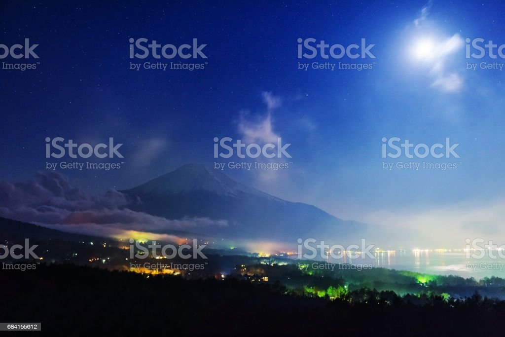 Mt. Fuji and lake Yamanaka from Fuji Panoramadai viewpoint at night with shrining stars and moon, Yamanashi royalty free stockfoto