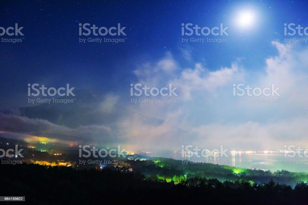 Mt. Fuji and lake Yamanaka from Panoramadai viewpoint at night with shrining stars, mist, and moon, royaltyfri bildbanksbilder