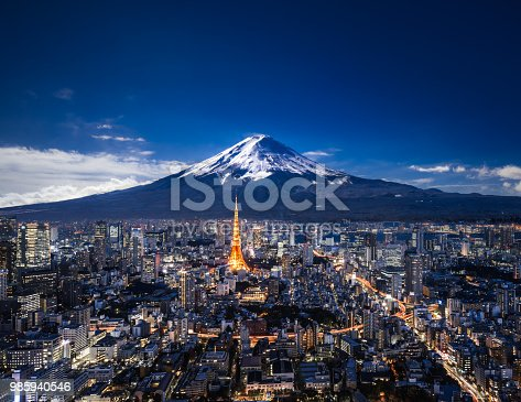 Elevated view of Mt. Fuji and modern skyscrapers in Tokyo at night.