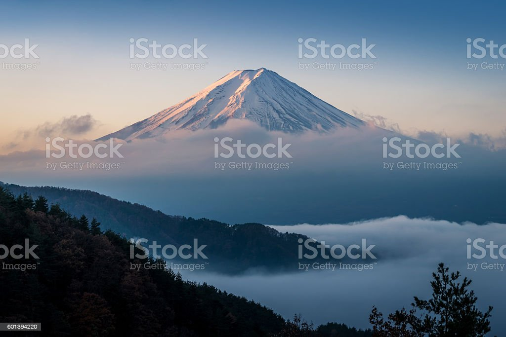 Mt. Fuji enshrouded in clouds with clear sky stock photo