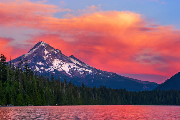 Mt. Hood at sunset from Lost Lake, Oregon. Mt. Hood at sunset with the snowcapped mountain peak and dramatic, orange sky and clouds from the shore of Lost Lake, Oregon. mt hood stock pictures, royalty-free photos & images
