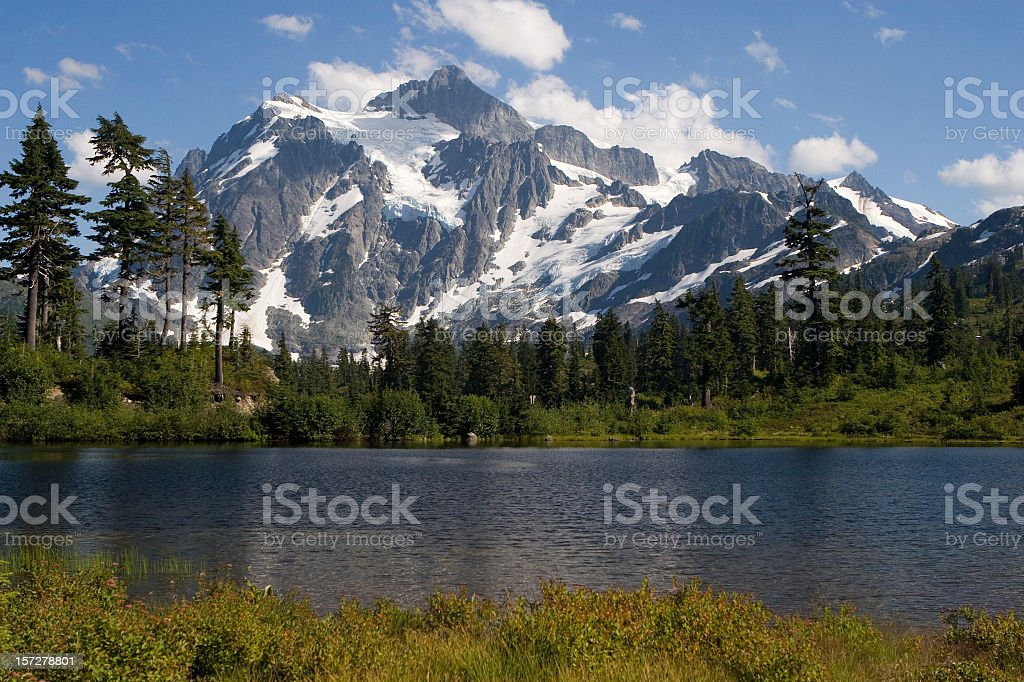 Mt Shuksan in summer with snow and lake stock photo