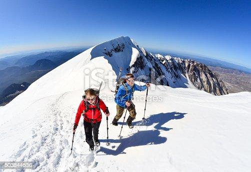 A woman and man traverse the summit ridge of Mt. St. Helens, Washington State.