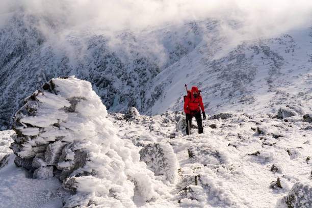 Mt. Washington Winter Climb This photo was taken on new years eve during a winter climb of Mt. Washington NH. The model Elizabeth Moats was just below the summit in the alpine garden. The sunlight and clouds were beautiful. mount washington new hampshire stock pictures, royalty-free photos & images