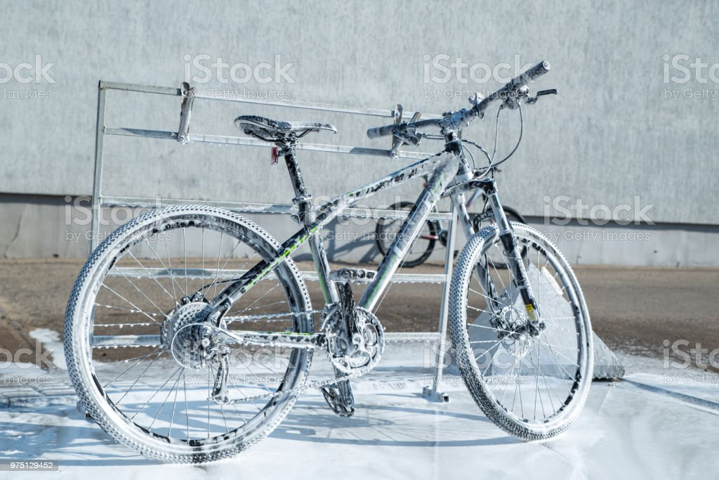 mtb bicycle in soap. self-service. bicycle washing stock photo