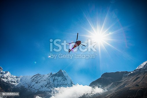 istock Mt.Machapuchare and helicopter with the sun 803888544