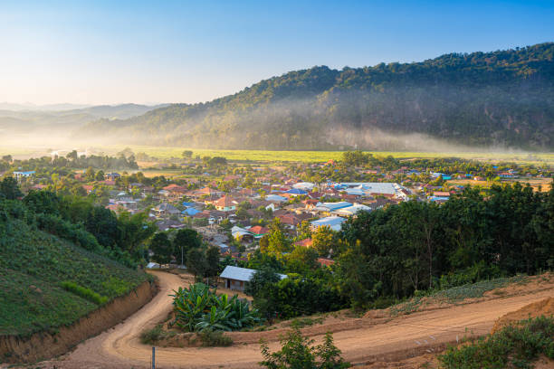 Muang Long village in the golden triangle, Luang Namtha North Laos near China Burma Thailand, small town in river valley with scenic mist and fog. Travel destination for tribal trekking in Akha villages stock photo