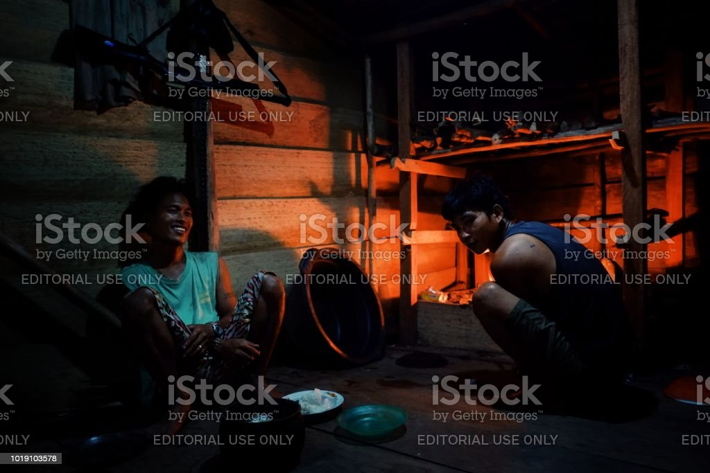 Muara Siberut, Mentawai Islands / Indonesia - Aug 15 2017: Liki and an other tribal boy is preparing the dinner in their jungle home stock photo
