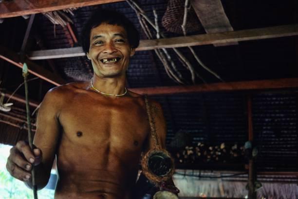 muara siberut, mentawai-inseln / indonesien - 15. august 2017: tribal toikots sohn aman vorbereitung für die jagd im dschungel - affentattoos stock-fotos und bilder