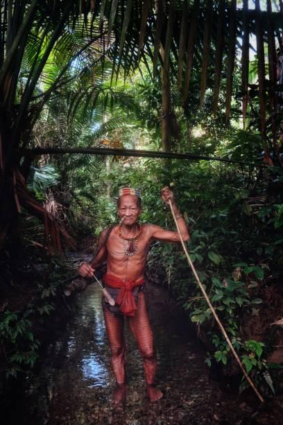 muara siberut, mentawai-inseln / indonesien - 15. august 2017: tribal jäger toikot auf der jagd auf affen in der mitte einen stream tief im dschungel - affentattoos stock-fotos und bilder