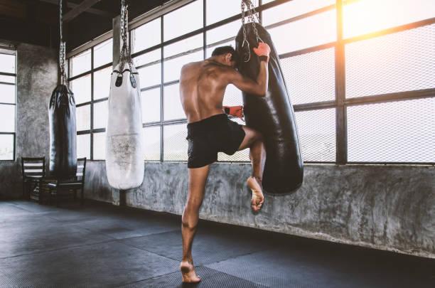 Muay thai Kämpfer Training in der Turnhalle mit dem Boxsack – Foto
