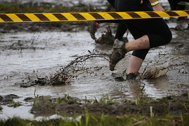 Mud A muddy trainer leaves a trail as a racer makes their way through a puddle.  mud run stock pictures, royalty-free photos & images