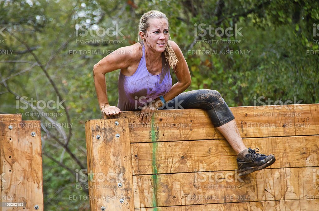 Mud race participant at a wall obstacle stock photo