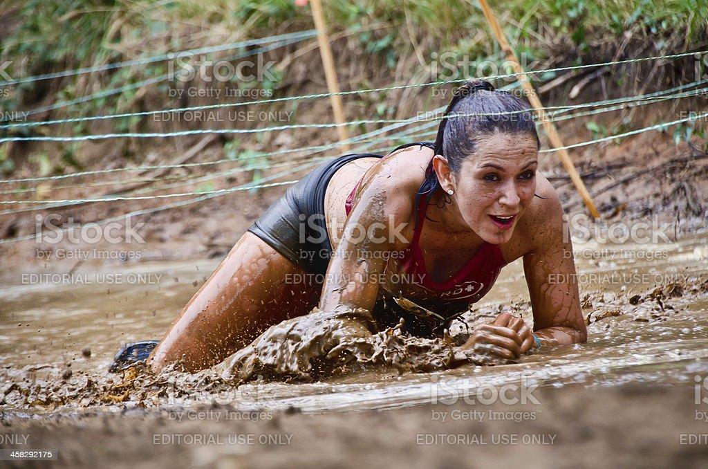 Mud race participant crawling under the wires stock photo