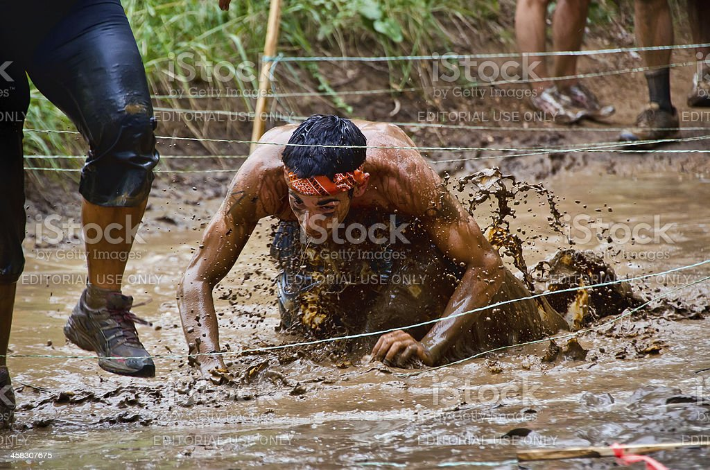 Mud race participant crawling under wires stock photo