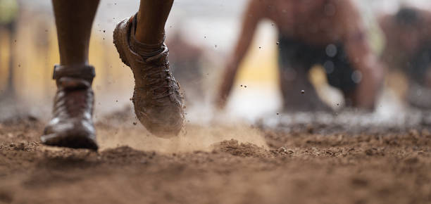 Mud race runners Mud race runners.Crawling,passing under a barbed wire obstacles during extreme obstacle race obstacle course stock pictures, royalty-free photos & images