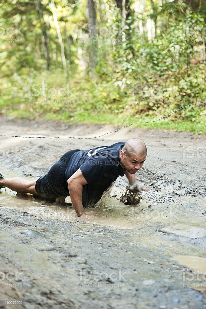 Mud Racing under barb wire stock photo