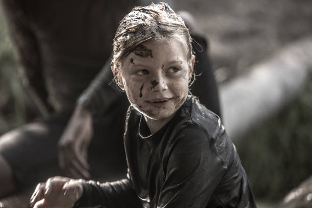 Mud Run Child Individual pre-teen child having sporty fun at a public mud run obstacle course mud run stock pictures, royalty-free photos & images