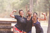 Three female teammates pose midway through a mud run competition. to flex their muscles and show off their muddy bodies.