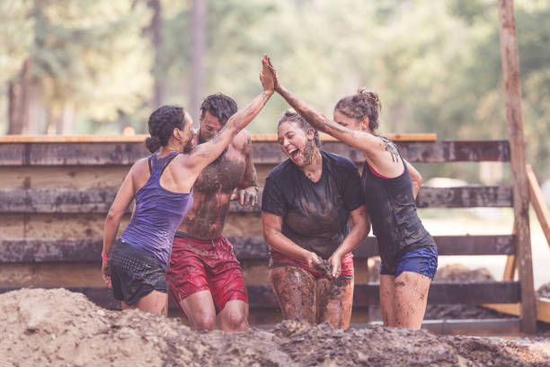 Mud Run in the Wild Three females pose with their bearded male teammate midway through a mud run competition. They are covered in water and mud...and are smiling cheerfully as they high-five and push each other over. mud run stock pictures, royalty-free photos & images